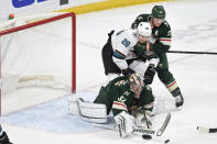 Minnesota Wild's Ryan Suter, right, holds off the San Jose Sharks' Timo Meier (28), of Switzerland, as the Wild's goalie Alex Stalock makes a save in the first period of an NHL hockey game, Saturday, Feb. 15, 2020, in St. Paul, Minn. (AP Photo/Tom Olmscheid)