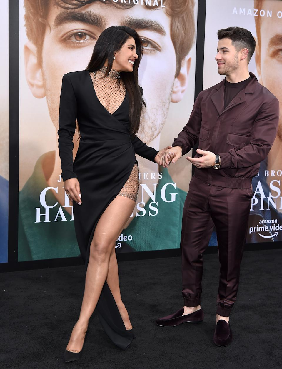 Priyanka took the thigh-high split trend to the next level in this black gown. Meanwhile husband Nick dressed down in a burgundy look by Ermenegildo Zegna.<em> [Photo: Getty]</em>