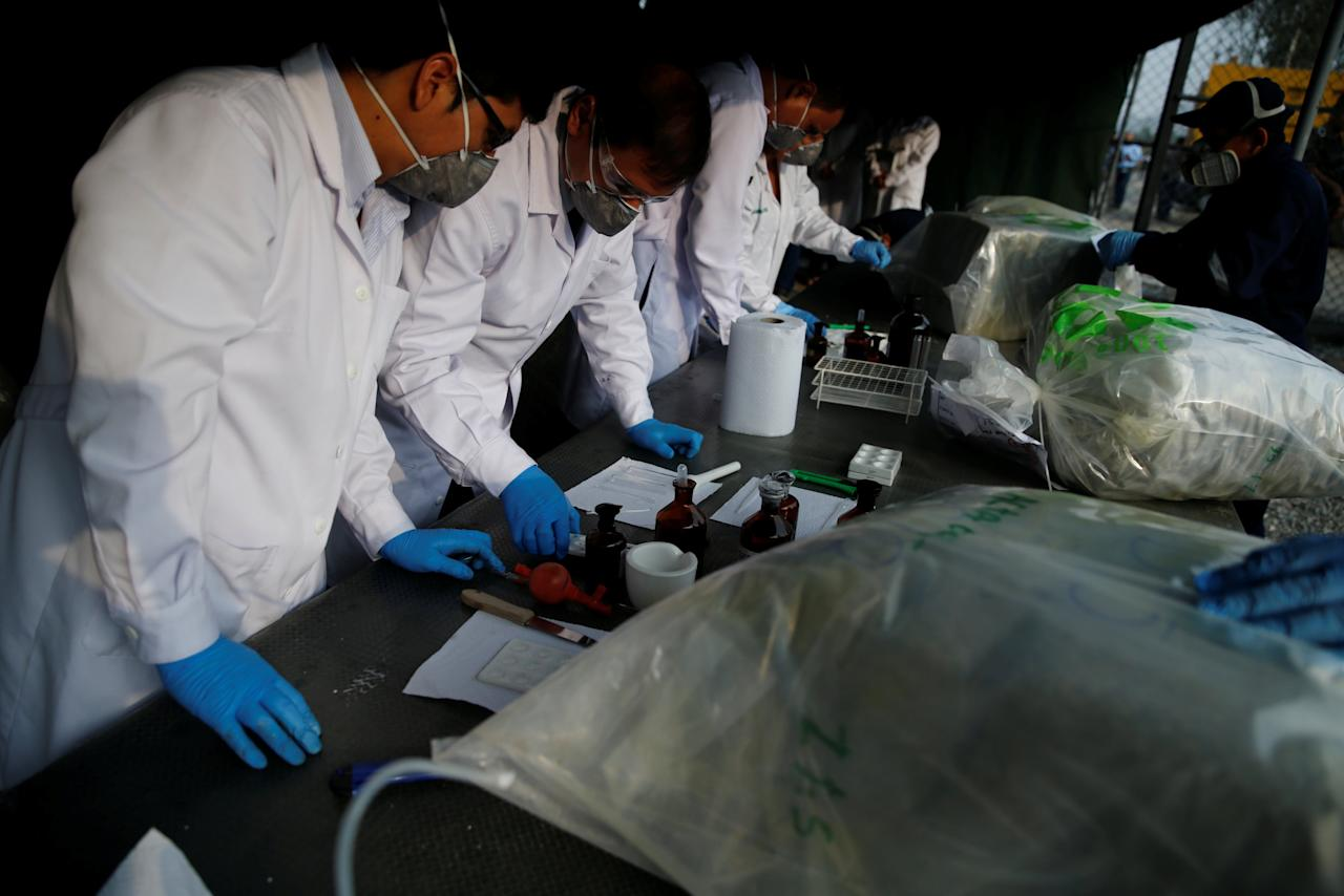 Anti-narcotics workers test cocaine before the incineration of about 8 tons of drugs seized during police operations, according to the Interior Ministry, in Lima, Peru March 30, 2017. REUTERS/Guadalupe Pardo