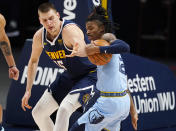 Memphis Grizzlies guard Ja Morant, right, steals the ball from Denver Nuggets center Nikola Jokic in the first half of an NBA basketball game Monday, April 19, 2021, in Denver. (AP Photo/David Zalubowski)