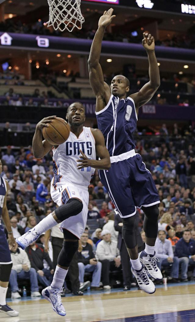 Charlotte Bobcats' Kemba Walker (15) drives past Oklahoma City Thunder's Serge Ibaka (9) during the first half of an NBA basketball game in Charlotte, N.C., Friday, Dec. 27, 2013. (AP Photo/Chuck Burton)