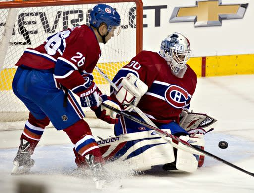 Montreal Canadiens goalkeeper Peter Budaj, right, makes a save against the Carolina Hurricanes while teammate Josh Gorges stands by during the first period of a preseason NHL hockey game Friday, Sept. 20, 2013, in Quebec City. (AP Photo/The Canadian Press, Jacques Boissinot)