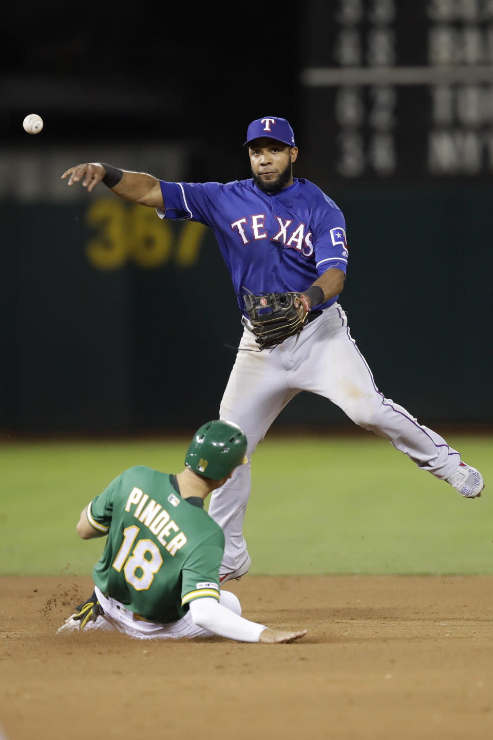 Texas Rangers' Elvis Andrus throws over Oakland Athletics' Chad Pinder (18) to complete a double play in the fourth inning of a baseball game Friday, Sept. 20, 2019, in Oakland, Calif. Sheldon Neuse was out at first. (AP Photo/Ben Margot)
