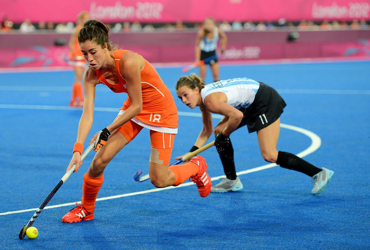 LONDON, ENGLAND - AUGUST 10: Naomi Van As #18 of Netherlands controls the ball against Carla Rebecchi #11 of Argentina during the Women's Hockey gold medal match on Day 14 of the London 2012 Olympic Games at Hockey Centre on August 10, 2012 in London, England.  (Photo by Mike Hewitt/Getty Images)