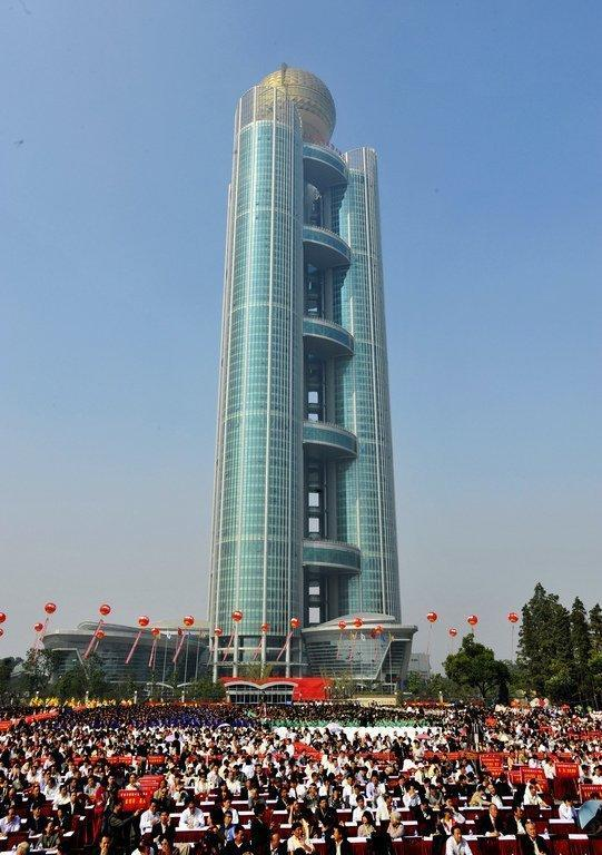 This file photo shows guests attending the opening ceremony of the Longxi International Hotel, standing at 328 m high, that cost $470 mln to build, in Huaxi, which is still classed as a village in east China's Jiangsu province, on October 8, 2011. One of China's tallest buildings opened for business in the nation's 'wealthiest village,' a symbol of the country's breakneck economic growth