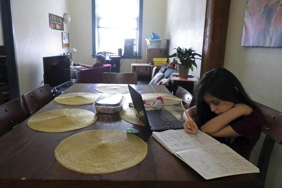 Veronica Esquivel, 10, finishes her homework after her virtual school hours while her brother Isias Esquivel sits in front of his computer, Wednesday, Feb. 10, 2021, at their residence in Chicago's predominantly Hispanic Pilsen neighborhood. Her mother, Rosa, worries that her diabetes and her husband's high blood pressure could put their lives at risk if their kids brought the coronavirus home from school. (AP Photo/Shafkat Anowar)