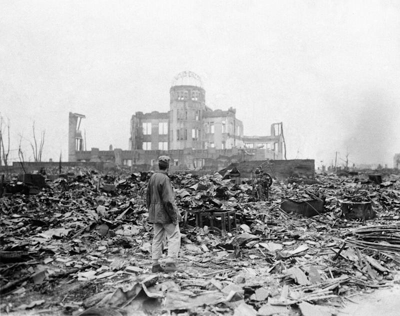 An allied correspondent stands in the rubble in front of the shell of a building that once was a exhibition center and government office in Hiroshima, Japan, a month after the first atomic bomb.