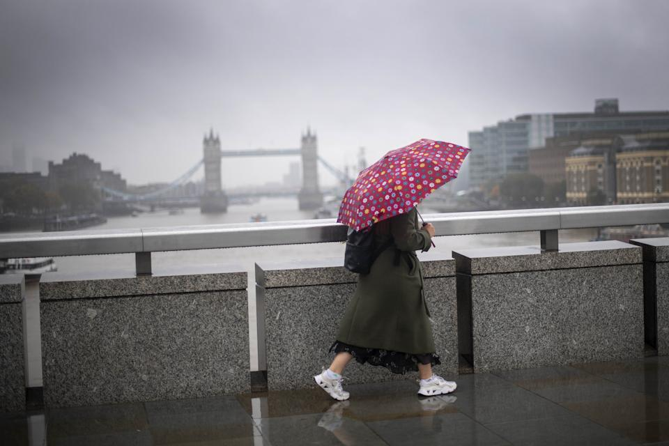 A morning commuter crosses London Bridge in central London