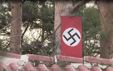 Swastika flags hang in the garden of the Nazi house.