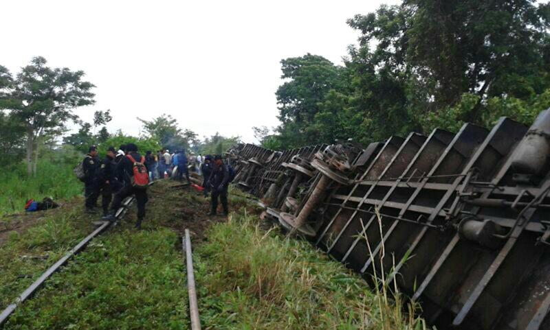 """In this photo release by the Civil Protection of the State of Tabasco, police agents work at a site where a train derailed in Tabasco, Mexico, Sunday, Aug. 25, 2013. An cargo train known as """"The Beast,"""" carrying at least 250 Central American migrants heading to the U.S. derailed in a remote region of southern Mexico on Sunday, killing five and injuring 16, authorities said. (AP Photo/Civil Protection of the State of Tabasco)"""