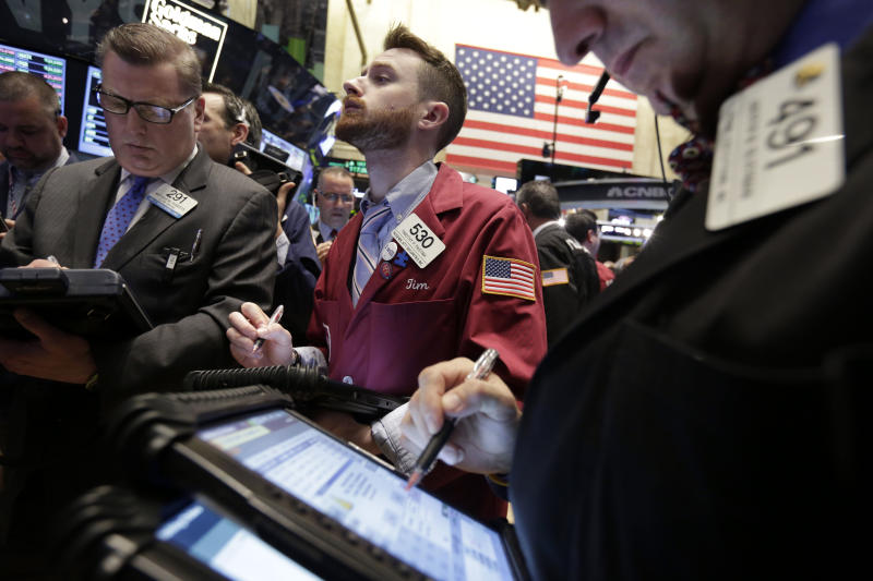 Trader Timothy Pastina, center, works on the floor of the New York Stock Exchange Friday, April 4, 2014. Stocks are edging mostly higher in early trading Friday after the government reported that U.S. employers added to their payrolls last month. (AP Photo/Richard Drew)