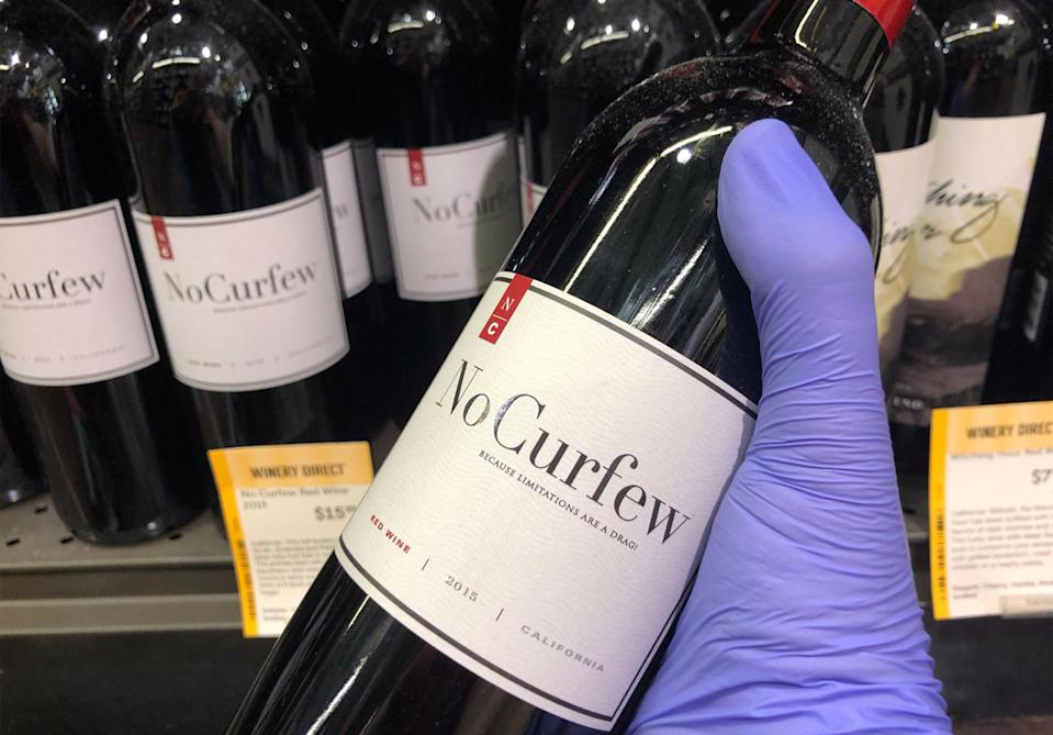 """A customer wearing a glove grabs the wine """"No Curfew"""" at the Total Wine & More liquor store in South Beach, Miami, on March 19, 2020. - Liquor sales have exploded in the United States since a national emergency was declared with the closure of many theatres, bars and restaurants, while virtual cocktail parties with """"quarantinis"""" are on the rise. (Photo by Leila MACOR / AFP) (Photo by LEILA MACOR/AFP via Getty Images)"""