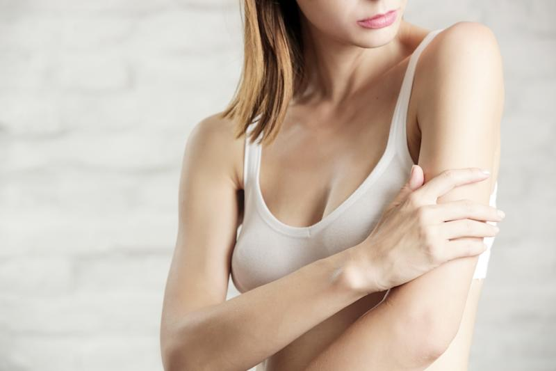 Photo of a young attractive woman touching her arm, dry or dehydrated skincare concept