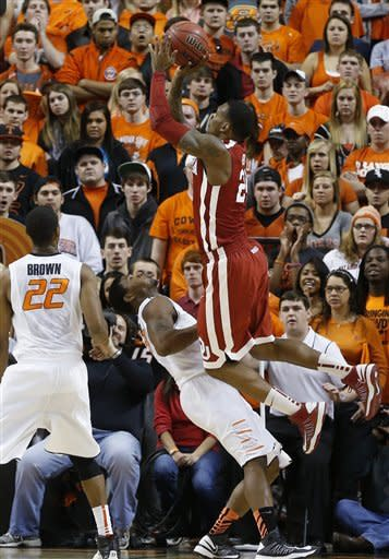 Oklahoma forward Romero Osby (24) shoots over Oklahoma State guard Marcus Smart (33) as guard Markel Brown (22) looks on, in the first half of an NCAA college basketball game in Stillwater, Okla., Saturday, Feb. 16, 2013. (AP Photo/Sue Ogrocki)
