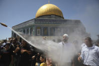 Worshippers are cooled by mist at the last Friday prayers of the Muslim holy month of Ramadan at the Dome of the Rock Mosque in the Al Aqsa Mosque compound in the Old City of Jerusalem, Jerusalem, Friday, May 7, 2021. (AP Photo/Mahmoud Illean)