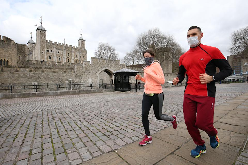 Joggers by a quiet Tower of London, as the UK's coronavirus death toll reached 144 as of 1pm on Thursday, with around four in 10 of all deaths so far in London. (Photo by Jonathan Brady/PA Images via Getty Images)