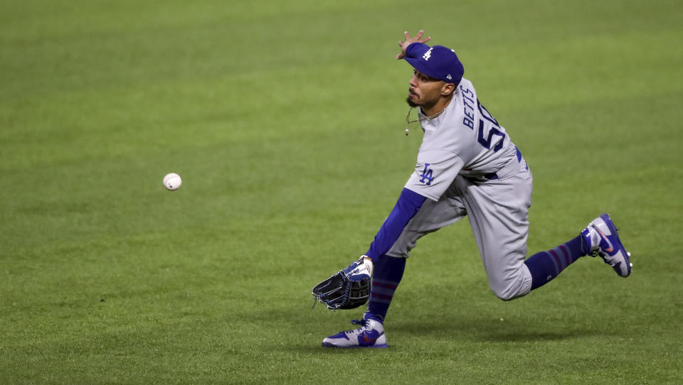 Los Angeles Dodgers right fielder Mookie Betts (50) catches a fly ball from Atlanta Braves shortstop Dansby Swanson then throws to home in the third inning of Game 5 of a baseball National League Championship Series, Friday, Oct. 16, 2020, in Arlington, Texas. (Curtis Compton/Atlanta Journal-Constitution via AP)