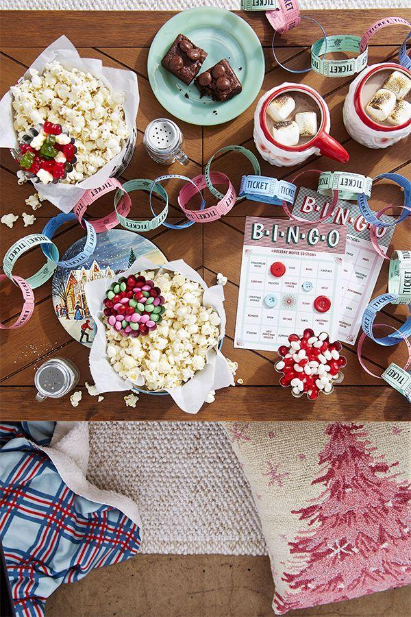"<p>Think outside the dining room! From a ticket garland to theater-candy brownies, this cozy flick-themed gathering (complete with <a href=""https://www.countryliving.com/life/entertainment/a34555161/christmas-bingo/"" rel=""nofollow noopener"" target=""_blank"" data-ylk=""slk:downloadable bingo cards"" class=""link rapid-noclick-resp"">downloadable bingo cards</a>) makes movie viewing more memorable. Vintage cookie tins make festive individual popcorn ""bowls."" Set out a selection of comfy pillows and warm blankets for snuggling up while viewing.</p><p><a class=""link rapid-noclick-resp"" href=""https://www.amazon.com/Christmas-Farmhouse-Decorations-Buffalo-Watercolor/dp/B08DXVWWV5/ref=sr_1_7?dchild=1&keywords=christmas+pillows&qid=1603379850&sr=8-7&tag=syn-yahoo-20&ascsubtag=%5Bartid%7C10050.g.644%5Bsrc%7Cyahoo-us"" rel=""nofollow noopener"" target=""_blank"" data-ylk=""slk:SHOP CHRISTMAS PILLOWS"">SHOP CHRISTMAS PILLOWS</a></p>"