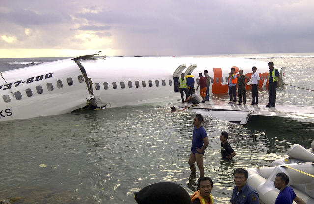 In this photo released by Indonesia's National Rescue Team, rescuers stand near the wreckage of a crashed Lion Air plane in Bali, Indonesia on Saturday, April 13, 2013. The plane carrying more than 100 passengers and crew overshot a runway on the Indonesian resort island of Bali on Saturday and crashed into the sea, injuring nearly two dozen people, officials said. (AP Photo/National Rescue Team)