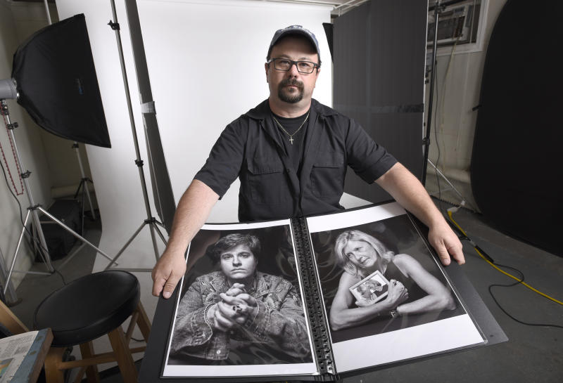 "In this June 21, 2019, photo, Paul Gillespie, a photojournalist at the Capital Gazette newspaper, where five people were killed in a mass shooting in June 2018, holds a book of portraits he photographed of survivors and family members of those killed in the attack, at his home studio in Brooklyn Park, Md. It's called: ""Journalists Matter: Faces of the Capital Gazette.""  (AP Photo/Steve Ruark)"