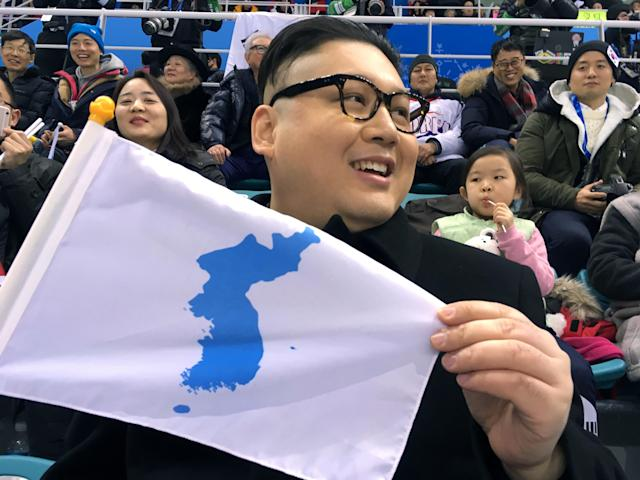 A Kim Jong Un impersonator, calling himself only Howard from Australia, holds a unification flag while attending the Korea-Japan women's ice hockey game at the 2018 Winter Olympics in Pyeongchang, South Korea on Wednesday. (AP)