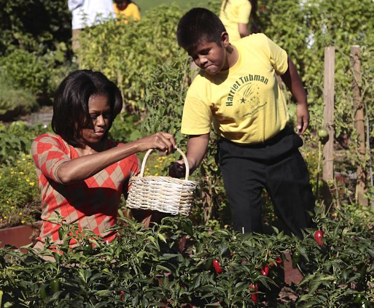 FILE - In this Oct. 5, 2011, file photo, first lady Michelle Obama gets help from fifth grade student Sterling Zapata in filling a basket with peppers in the White House garden in Washington. From the beginning, Obama's kitchen garden has been an overachiever, churning out more peppers, parsley and eggplant than expected, and generating interest that _ yes, really _ crosses oceans. (AP Photo/Pablo Martinez Monsivais, File)