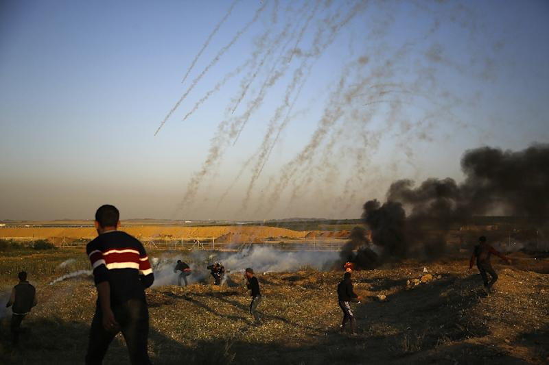 Palestinian protesters run from tear gas fired by Israeli forces during clashes along the border with Israel, east of Gaza City on April 1, 2018 hundreds more when a major demonstration led to clashes along the border with the Gaza Strip (AFP Photo/Mohammed ABED)