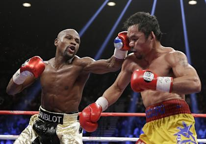 Floyd Mayweather Jr. (L) hits Manny Pacquiao during their welterweight title fight. (AP)