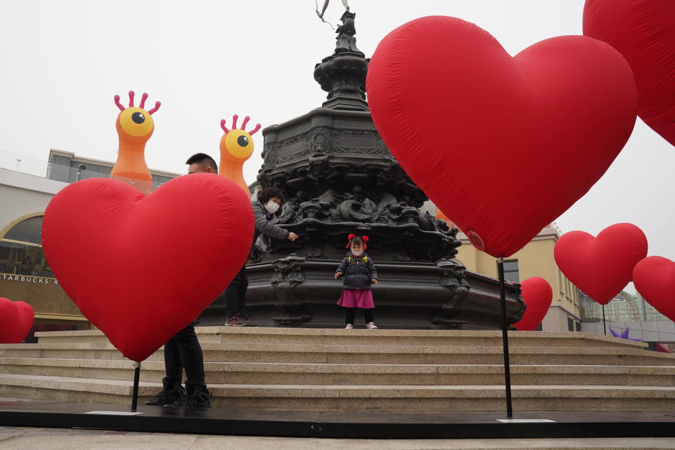 A visitor wearing a mask to protect from the coronavirus stand near heart shaped balloons displayed at a mall district during the second day of the Chinese Lunar New Year in Beijing on Saturday, Feb. 13, 2021. (AP Photo/Ng Han Guan)