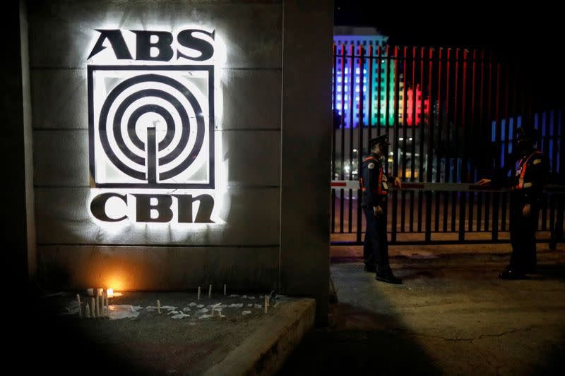 FILE PHOTO: Security guards stand outside the headquarters of ABS-CBN network following government orders to cease its operations, in Quezon City