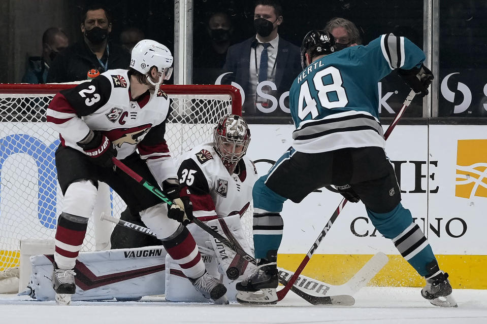 Arizona Coyotes goaltender Darcy Kuemper (35) blocks a shot by San Jose Sharks center Tomas Hertl (48) as Oliver Ekman-Larsson (23) defends during the second period of an NHL hockey game Friday, May 7, 2021, in San Jose, Calif. (AP Photo/Tony Avelar)
