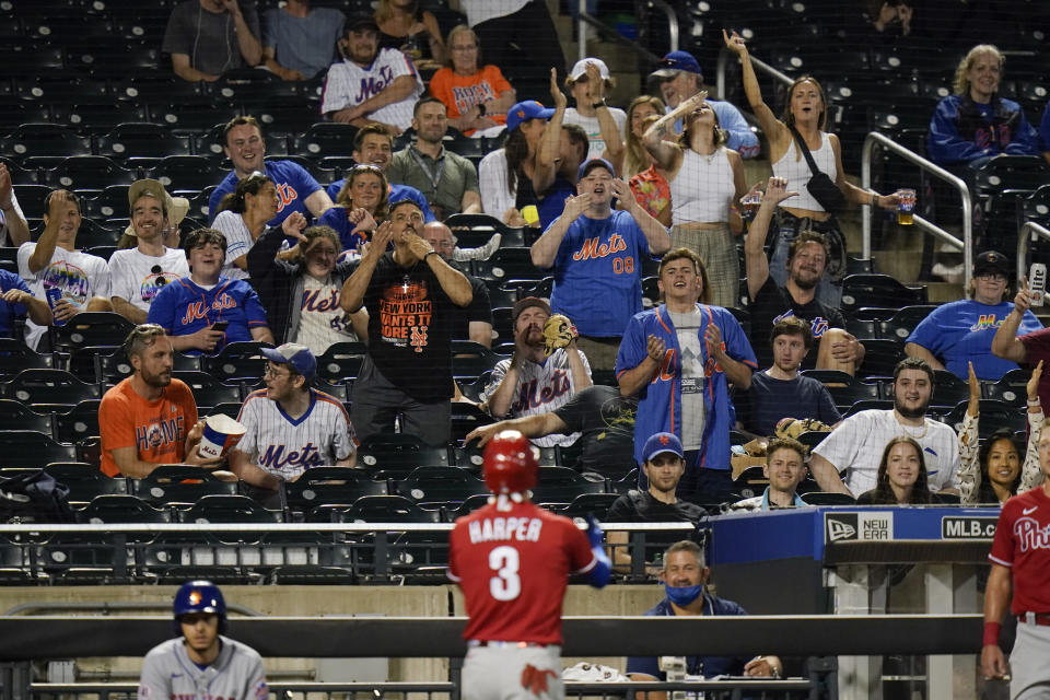 New York Mets fans react toward Philadelphia Phillies' Bryce Harper after Harper hit a home run during the sixth inning of the second baseball game of a doubleheader against the New York Mets Friday, June 25, 2021, in New York. (AP Photo/Frank Franklin II)