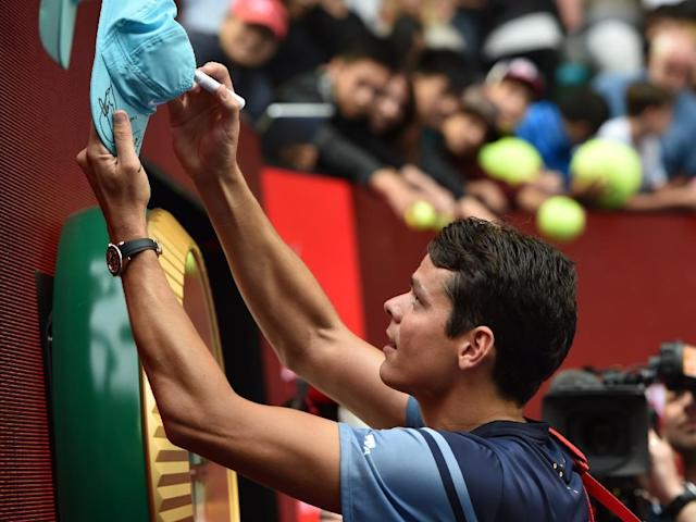 Canada's Milos Raonic signs autographs for fans following his Australian Open men's singles fourth round victory against Switzerland's Stanislas Wawrinka, in Melbourne, on January 25, 2016 (AFP Photo/Saeed Khan)
