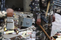 A safe of a shop lie outside after it was ransacked during riots as Indian paramilitary soldiers stand guard in New Delhi, India, Wednesday, Feb. 26, 2020. At least 20 people were killed in three days of clashes in New Delhi, with the death toll expected to rise as hospitals were overflowed with dozens of injured people, authorities said Wednesday. The clashes between Hindu mobs and Muslims protesting a contentious new citizenship law that fast-tracks naturalization for foreign-born religious minorities of all major faiths in South Asia except Islam escalated Tuesday. (AP Photo/Manish Swarup)