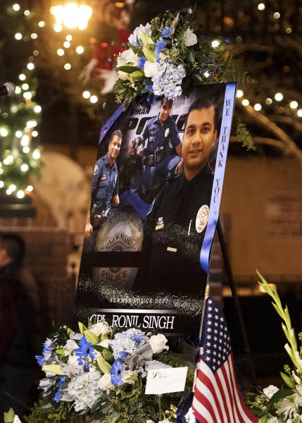 FILE - This Friday, Dec. 28, 2018 file photo shows a collection of pictures of police Cpl. Ronil Singh during a candlelight vigil in Newman, Calif. The Northern California police officer was gunned down during a traffic stop the day after Christmas 2018. (Andy Alfaro/The Modesto Bee via AP, File)