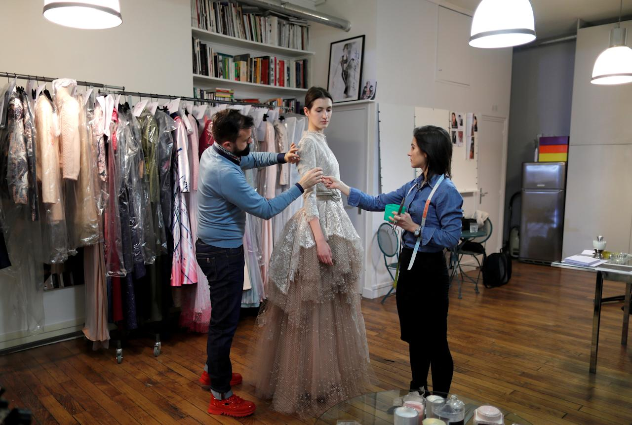 French designer Julien Fournie (L) adjusts a creation on model Greta (C) during a fitting at his workshop ahead of his Spring-Summer 2018 Haute Couture fashion show presentation in Paris, France, January 15, 2018. Picture taken January 15, 2018.  REUTERS/Charles Platiau