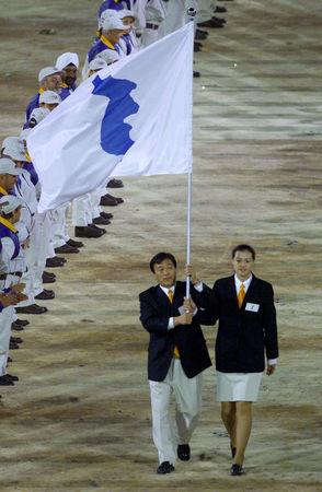FILE PHOTO: For the first time in Olympic history athletes from North and South Korea joined hands and marched together under one flag during the opening ceremony of the XXVII Summer Olympic Games, Sydney, Australia September 15, 2000. REUTERS/David Gray/File Photo