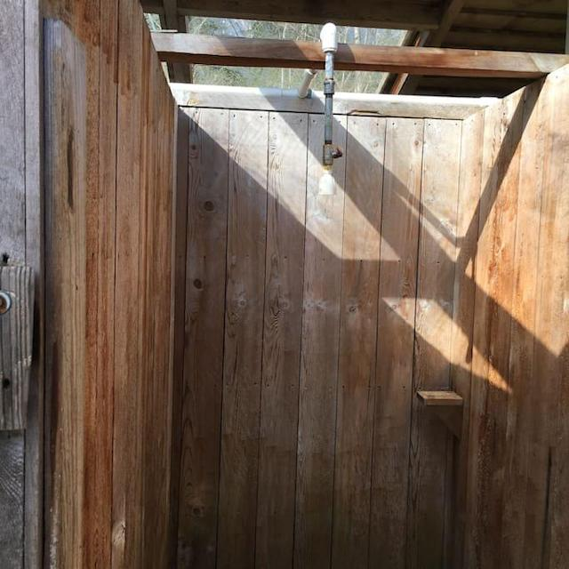 <p>The tent even has little camping luxuries, like this cedar outdoor shower. (Airbnb) </p>