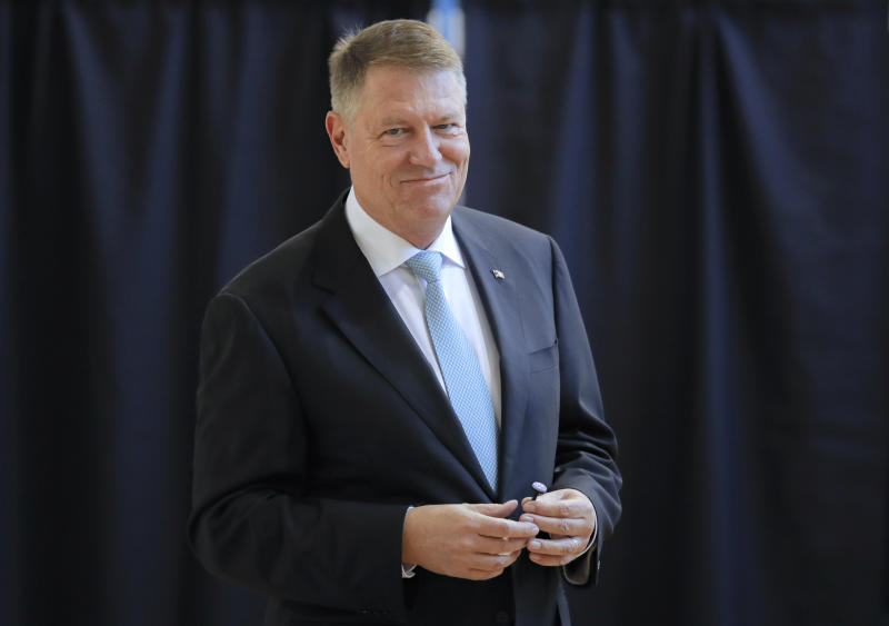 Romanian President Klaus Iohannis smiles after casting his vote in Bucharest, Romania, Sunday, Nov. 10, 2019. Voting got underway in Romania's presidential election after a lackluster campaign overshadowed by a political crisis which saw a minority government installed just a few days ago. (AP Photo/Vadim Ghirda)