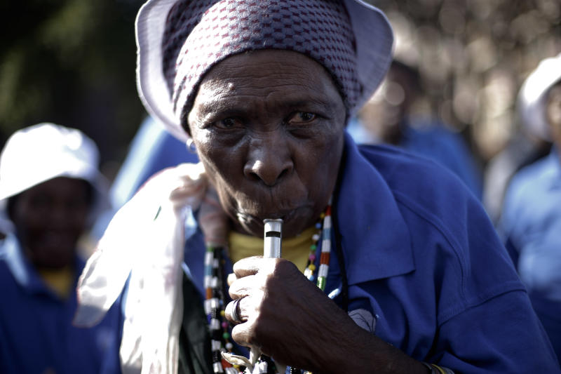 A woman dances and blows a whistle at the entrance of the Mediclinic Heart Hospital where former South African President Nelson Mandela is being treated in Pretoria, South Africa, Thursday, July 4, 2013. (AP Photo/Markus Schreiber)