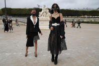 Fashion lovers strike a pose after Dior's Spring-Summer 2021 fashion collection presented Tuesday, Sept. 29, 2020 during the Paris fashion week. (AP Photo/Francois Mori)