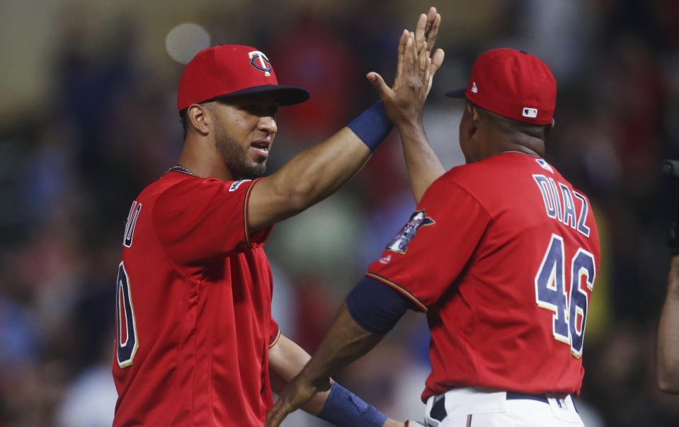 Minnesota Twins' Eddie Rosario, left, goes through the celebration line with a high-five from coach Tony Diaz after the Twins defeated the Oakland Athletics 6-3 in a baseball game Thursday, July 18, 2019, in Minneapolis. Rosario hit a three-run home run in the seventh inning off Athletics' Yusmeiro Petit, who took the loss. (AP Photo/Jim Mone)