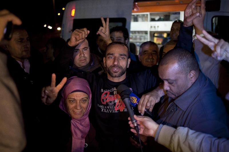 Palestinian prisoner Samer Issawi is surrounded by family after his release from Shita prison near Afula, northern Israel, Monday, Dec. 23, 2013, months after ending a massive hunger strike to protest his re-arrest in 2012, shortly after being freed in a prisoner swap with Israel. Israel accused him of membership in an illegal organization.(AP Photo/Ariel Schalit)