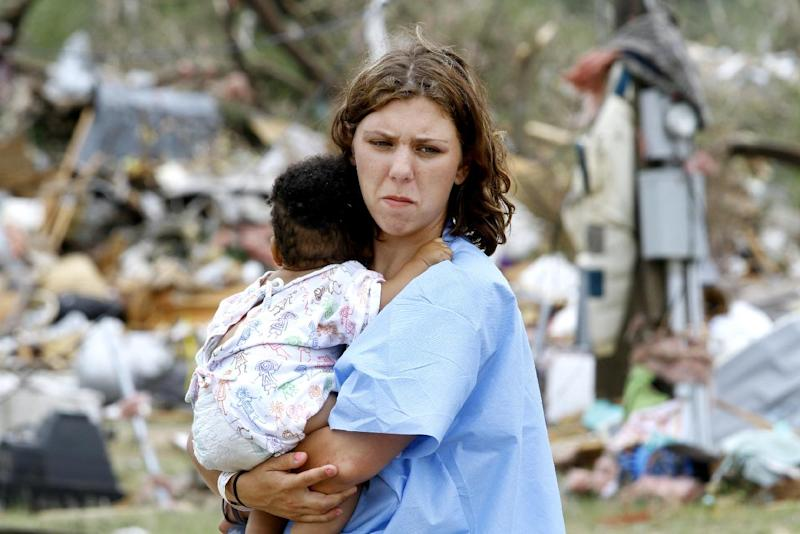 Kayla Holcey, right, holds her 8-month-old son Kristian Hampton as she looks at the debris that was once her home, Tuesday, April 29, 2014, in Crawford, Ala. Holcy said that she was terrified that her son had been killed until she heard his cries under the rubble. A tornado tore through the Crawford community before dawn. (AP Photo/The Ledger-Enquirer, Robin Trimarchi) MANDATORY CREDIT