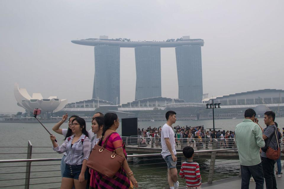 """Tourists snap selfies across the water from the haze shrouded Marina Bay Sands integrated resort on 14 September. Read our story: <a href=""""https://bit.ly/37p7xQb"""" rel=""""nofollow noopener"""" target=""""_blank"""" data-ylk=""""slk:https://bit.ly/37p7xQb"""" class=""""link rapid-noclick-resp"""">https://bit.ly/37p7xQb</a> (PHOTO: Dhany Osman / Yahoo News Singapore)"""
