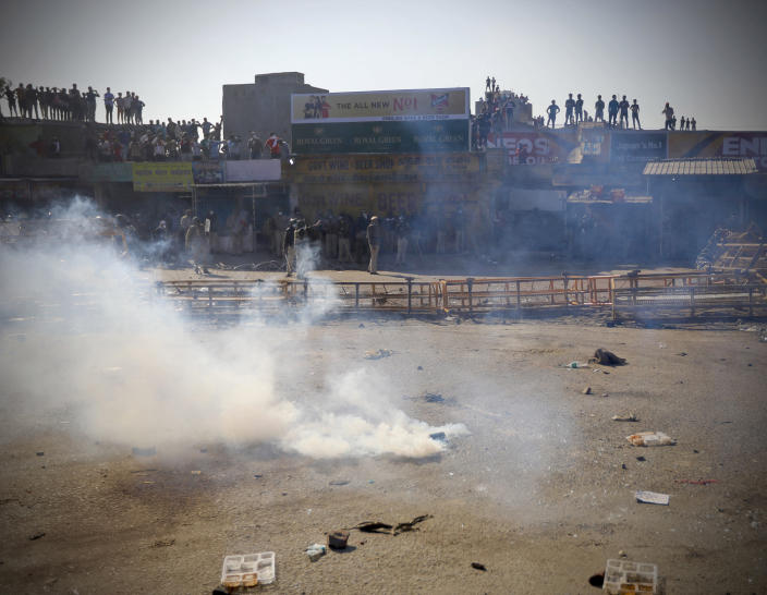 A tear gas shell explodes near policemen after it was thrown back by protesting farmers, at the border between Delhi and Haryana state, Friday, Nov. 27, 2020. Thousands of agitating farmers in India faced tear gas and baton charge from police on Friday after they resumed their march to the capital against new farming laws that they fear will give more power to corporations and reduce their earnings. While trying to march towards New Delhi, the farmers, using their tractors, cleared concrete blockades, walls of shipping containers and horizontally parked trucks after police had set them up as barricades and dug trenches on highways to block roads leading to the capital. (AP Photo/Manish Swarup)