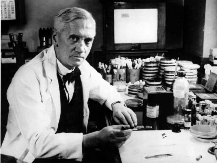 Alexander Fleming seated, wearing a white lab coat.