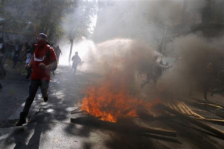 Student protesters run away during a demonstration to demand changes in the Chilean education system, in Santiago May 8, 2014. REUTERS/Ivan Alvarado