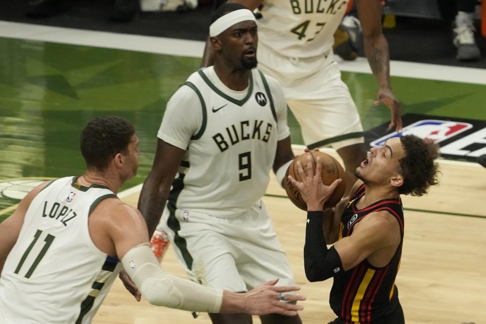 Atlanta Hawks' Trae Young tries to drive past Milwaukee Bucks' Brook Lopez and Bobby Portis during the first half of Game 2 of the NBA Eastern Conference basketball finals game Friday, June 25, 2021, in Milwaukee. (AP Photo/Morry Gash)