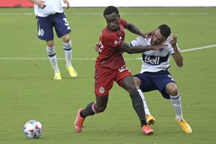 Toronto FC midfielder Richie Laryea (22) and Vancouver Whitecaps midfielder Caio Alexandre (8) compete for the ball during the second half of an MLS soccer match, Saturday, April 24, 2021, in Orlando, Fla. (AP Photo/Phelan M. Ebenhack)